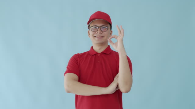 asian happy delivery man raise his hand thumb up and showing symbol is okay  isolated on blue colour background with smiling face.concept of postal delivery service. - isolated colour stock videos & royalty-free footage