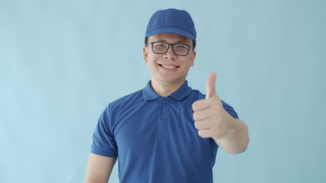 asian happy delivery man raise his hand thumb up and showing symbol is success  isolated on blue colour background with smiling face.concept of postal delivery service. - isolated colour stock videos & royalty-free footage