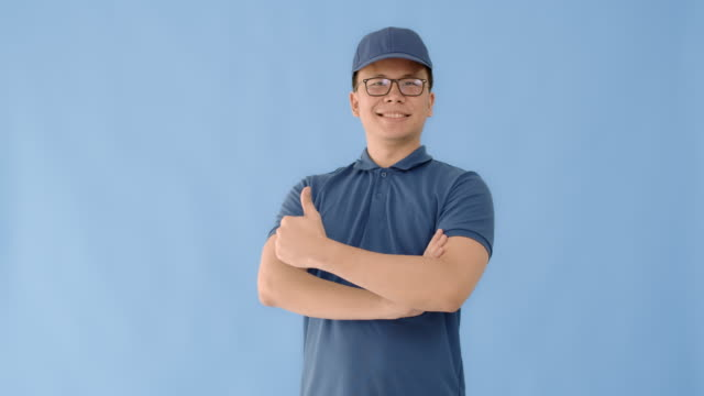 asian happy delivery man wearing a cap and a blue shirt carrying paper parcel boxes isolated on blue colour background with smiling face.concept of postal delivery service. - isolated colour stock videos & royalty-free footage