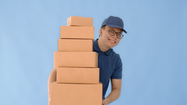 asian happy delivery man wearing a cap and a blue shirt carrying paper parcel boxes isolated on blue colour background with smiling face.concept of postal delivery service. - removal man stock videos & royalty-free footage