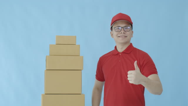 asian happy delivery man wearing a cap and a red shirt carrying paper parcel boxes isolated on blue colour background with smiling face.concept of postal delivery service. - isolated colour stock videos & royalty-free footage