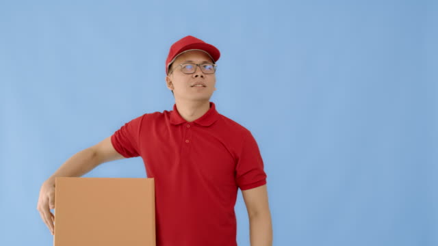 asian happy delivery man wearing a cap and a red shirt using smartphone and carrying paper parcel boxes isolated on blue colour background with smiling face.concept of postal delivery service. - isolated colour stock videos & royalty-free footage