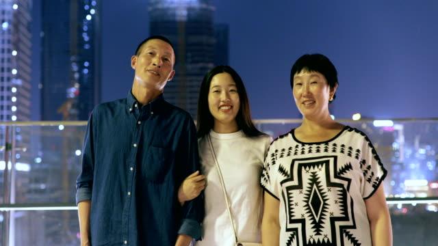 vídeos de stock, filmes e b-roll de asian happy family looking at camera at city night - de braços dados