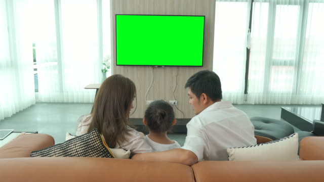 vídeos de stock e filmes b-roll de asian happy family sitting and watching television in living room at home and spent quality time together for activity in vacation day, holiday, happiness or lifestyle concept. - olhar atentamente