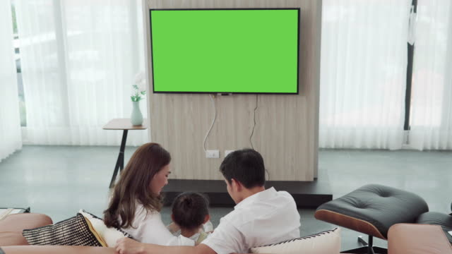 asian happy family sitting and watching television in living room at home and spent quality time together,channel to green screen monitor for your message - keyable stock videos & royalty-free footage