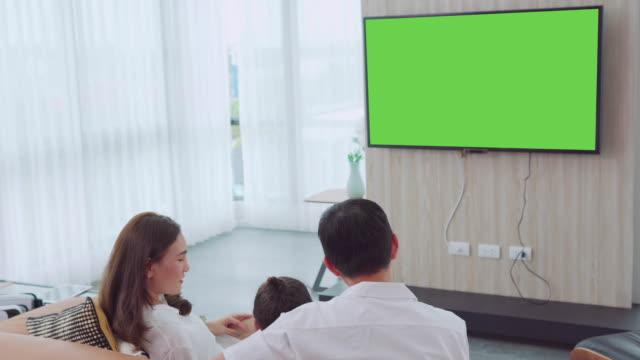 stockvideo's en b-roll-footage met aziatische gelukkige familie zitten en televisie kijken in woonkamer thuis en bracht quality time samen, channel to green screen monitor for your message - keyable