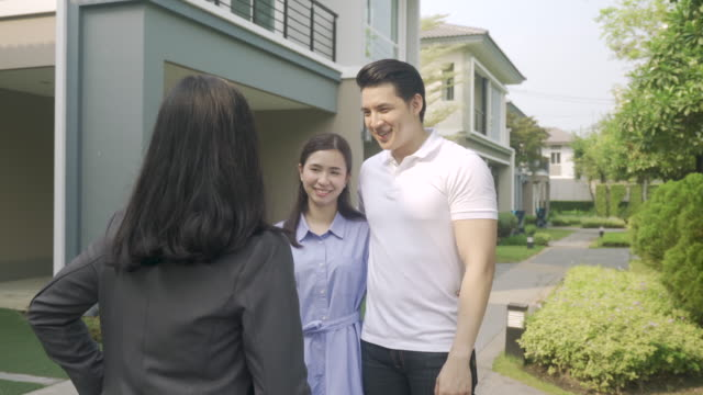 asian happy smile young couple take keys new big house from real estate agent or realtor in front of their house after signing contract agreement, concept for real estate, moving home or renting property - exchanging stock videos & royalty-free footage