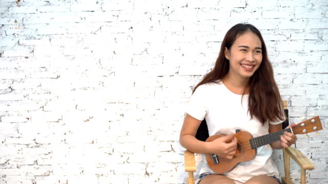 アジアの幸せな女性が白い背景でアコースティック ギターを演奏 - アコースティックギター点の映像素材/bロール