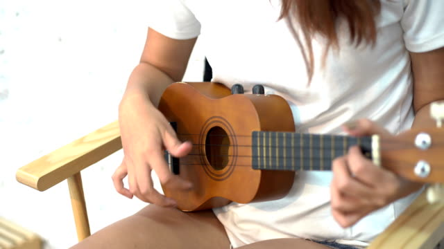 asiatische glückliche frauen spielt akustische gitarre mit weißem hintergrund - akkord stock-videos und b-roll-filmmaterial