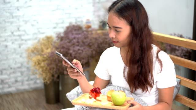 vídeos de stock, filmes e b-roll de mulheres asiáticas felizes usando telefone inteligente no quarto e beber café com rosquinhas e frutas - smart