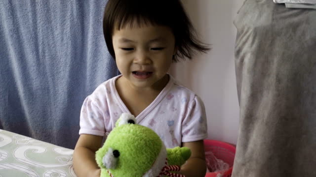 Asian Happy Young Girl With Green Frog Doll