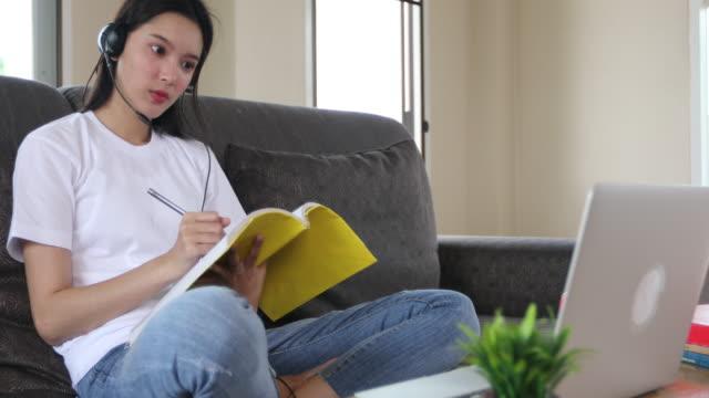 vídeos y material grabado en eventos de stock de asiática feliz joven estudiante usa auriculares estudio en línea viendo podcast webinar en la encuesta de aprendizaje de aprendizaje portátil conferencia de curso y escribir notas mirar a la computadora portátil sentado en el sofá en casa, e-learning  - clase de formación