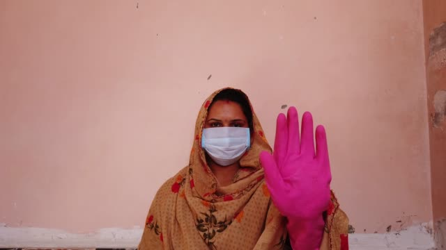 asian hindu woman in traditional costume wearing a mask and head covered gestures with her hands in gloves for protection and safety on the outbreak of the global coronavirus pandemic - gartenhandschuh stock-videos und b-roll-filmmaterial