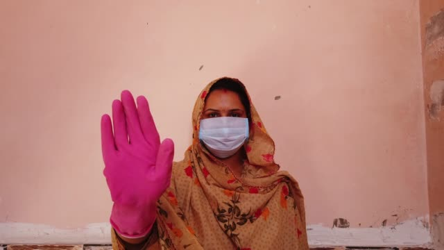 asian hindu woman in traditional costume wearing a mask and head covered gestures with her hands in gloves for protection and safety on the outbreak of the global coronavirus pandemic - gardening glove stock videos & royalty-free footage