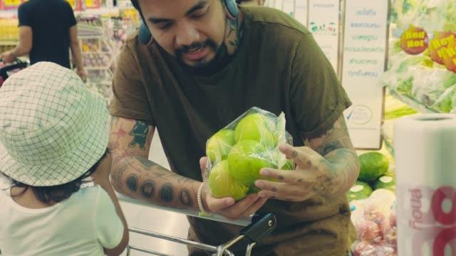 asian hipster father and child shopping for groceries. - mercato di prodotti agricoli video stock e b–roll