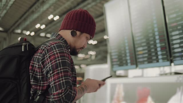 Asian hipster man checking departure board with smart phone at the airport