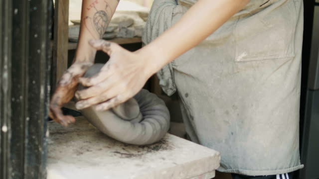 asian hipster potter is preparing clay for making and kneading clay in pottery workshop ceramic process-small business and craft product business concept - potter stock videos & royalty-free footage