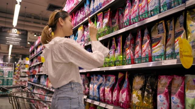 スーパーマーケットで買い物アジアのホーダーの女性 - 冷凍食品点の映像素材/bロール