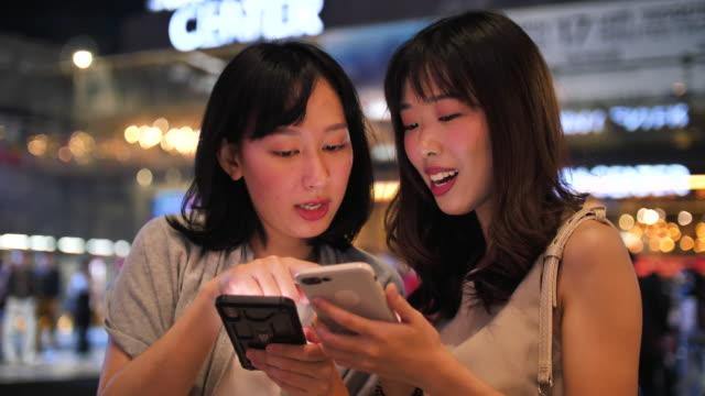 アジアの主婦は、購入を行うようにうわさ話や笑い - ホワイトカラー点の映像素材/bロール