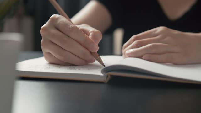 vídeos y material grabado en eventos de stock de mano humana asiática usando escritura a lápiz en cuaderno - una mujer de mediana edad solamente