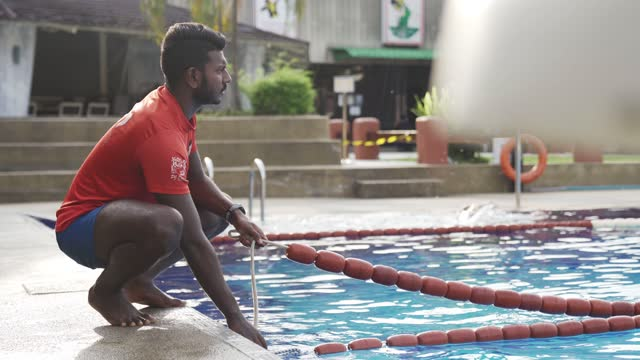 vídeos y material grabado en eventos de stock de socorrista indio asiático ajuste de la cuerda en la piscina preparándose - vigilante