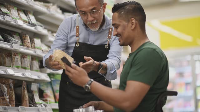 asian indian man with disability on wheelchair asking senior man retail assistant on his shopping list from smart phone at supermarket during weekend - buying stock videos & royalty-free footage