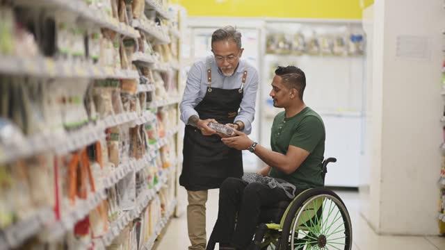 vidéos et rushes de homme indien asiatique handicapé en fauteuil roulant demandant à l'homme senior assistant de vente au détail sur sa liste de courses de téléphone intelligent au supermarché pendant le week-end - étal de marché