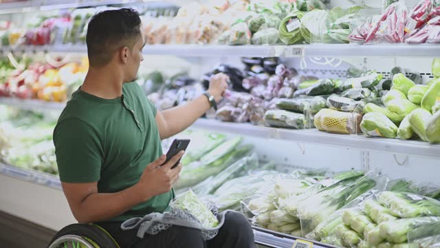 asian indian man with disability on wheelchair shopping at supermarket during weekend buying vegetables using smart phone - choice stock videos & royalty-free footage