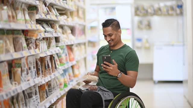vídeos de stock, filmes e b-roll de homem indiano asiático com deficiência em vídeo cadeira de rodas enquanto comprava em supermercado durante o fim de semana usando telefone inteligente - smart