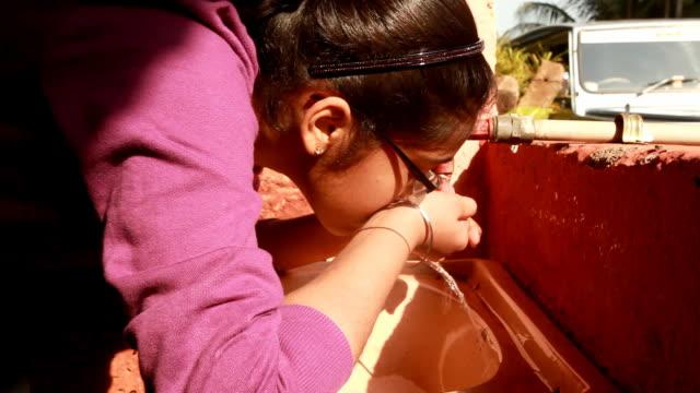"""vídeos de stock, filmes e b-roll de asiático indiano """"adolescente beber água da torneira - água potável"""