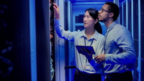 vídeos y material grabado en eventos de stock de ds asiático es ingeniero y su hombre compañero de trabajo comprobando el servidor debido a un problema reportado - equipo informático