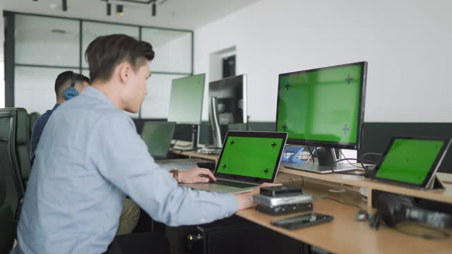 2 asian it professional support colleague working in office with multiple computer monitor screen - hot desking stock videos & royalty-free footage