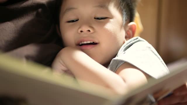 vidéos et rushes de l'enfant et la mère asiatiques lisent l'histoire d'heure du coucher dans la chambre à coucher. concept de temps en famille - littérature