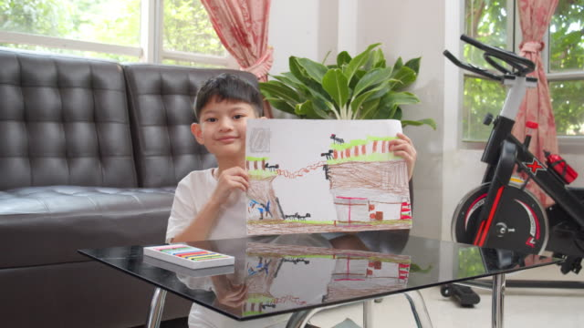 asian kid boy showing her finished drawing and painting art and craft in the living room while staying at home. he using oil pastel or chalk color to create art project in to white paper form her imagination. art and crafts concepts. - chalk art equipment stock videos & royalty-free footage