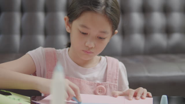 asian kid girl drawing and painting her art and craft in the living room while staying at home. she using oil pastel or chalk color to create art project in to paper form her imagination - chalk art equipment stock videos & royalty-free footage