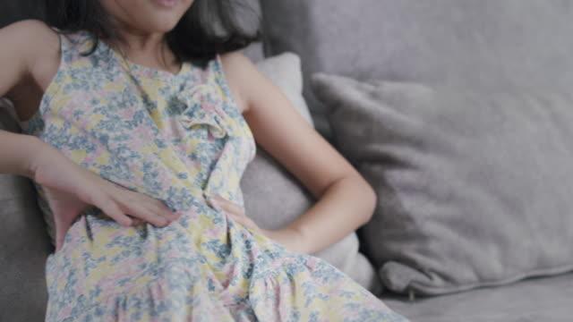 食中毒による腹痛を抱えているアジアの子供の女の子。自宅の居間のソファに座りながら、彼女は胃の痛みに手を握った。ファーストフードを食べた後に身体的な怪我をしたトゥイーンの女� - 盲腸点の映像素材/bロール