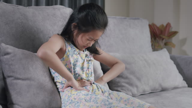 食中毒による腹痛を抱えているアジアの子供の女の子。自宅の居間のソファに座りながら、彼女は胃の痛みに手を握った。ファーストフードを食べた後に身体的な怪我をしたトゥイーンの女� - 虫垂点の映像素材/bロール