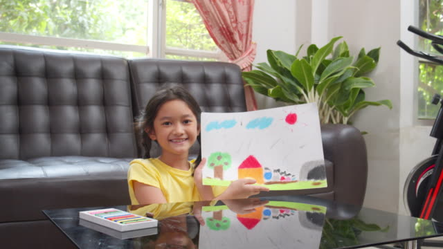asian kid girl showing her finished drawing and painting art and craft in the living room while staying at home. she using oil pastel or chalk color to create art project in to white paper form her imagination. art and crafts concepts. - chalk art equipment stock videos & royalty-free footage