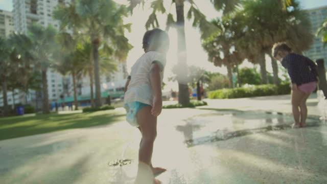 夏の日の噴水の間で楽しいアジアの子供。 - 噴水点の映像素材/bロール