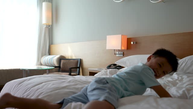 vídeos de stock, filmes e b-roll de garoto asiático pula no quarto do hotel. conceito de turismo e feriado - hotel