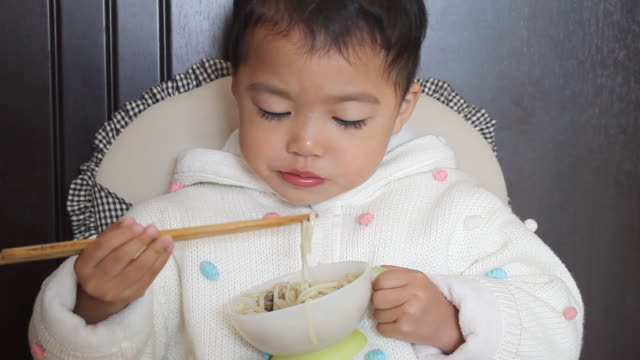 asian kid learning using chopsticks unskillfully to eat noodles