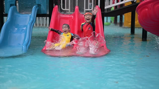 asian kid littile boy playing and having fun sliding a slider in water park - water slide stock videos & royalty-free footage