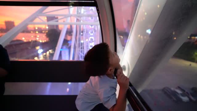 vídeos de stock, filmes e b-roll de garoto asiático na roda gigante à noite em bangkok. conceito de férias e sonho - roda gigante