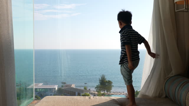 asian kid open curtain to see beautiful beach view. concept of tourism and holiday - hotel stock videos & royalty-free footage