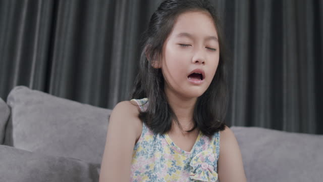 asian kid sneezing blowing her nose with a napkin from flu. she has allergy. young. girl sick with flu at home - mouth open stock videos & royalty-free footage