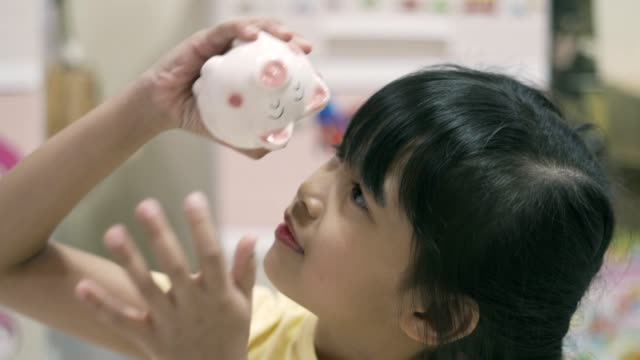 asian kid trying to get money out of piggy bank - bank stock videos & royalty-free footage