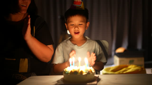 asian kid with his birthday cake. concept of celebration and joy - birthday candle stock videos & royalty-free footage