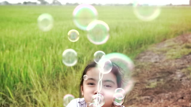 asian kids laughing and having fun in a summer green paddy field blowing bubbles, with slow motion - kids in a row stock videos & royalty-free footage
