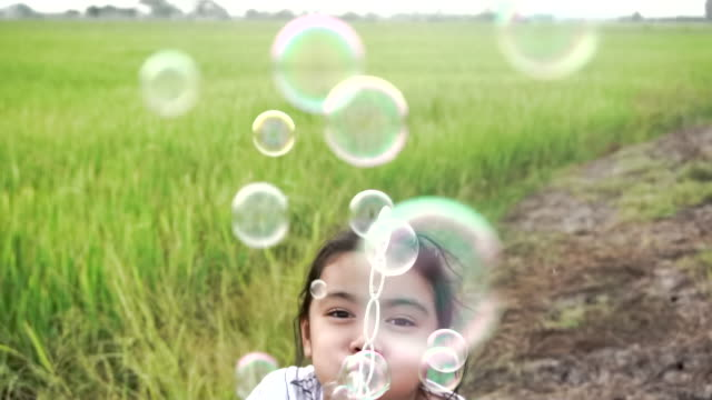 asian kids laughing and having fun in a summer green paddy field blowing bubbles, with slow motion stock video - bubble stock videos & royalty-free footage