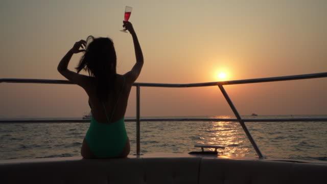signora asiatica che si gode e beve un cocktail sullo yacht. - barca da diporto video stock e b–roll